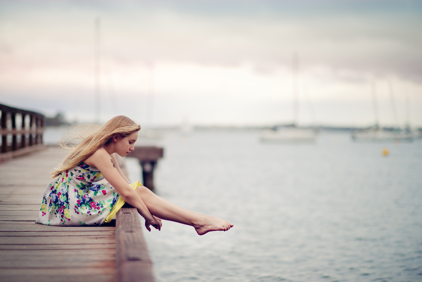 Girl sitting on a dock on a cloudy day