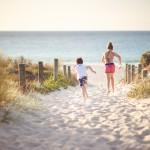 Children run through sand dunes towards the ocean