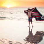 Boy standing with an outstretched towel at the beach at sunset