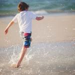 Boy splashing through water at the beach
