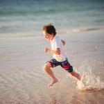 Boy running through water at the beach