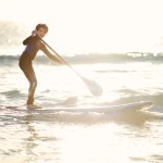 Boy rding wave on a stand up paddle board at sunset