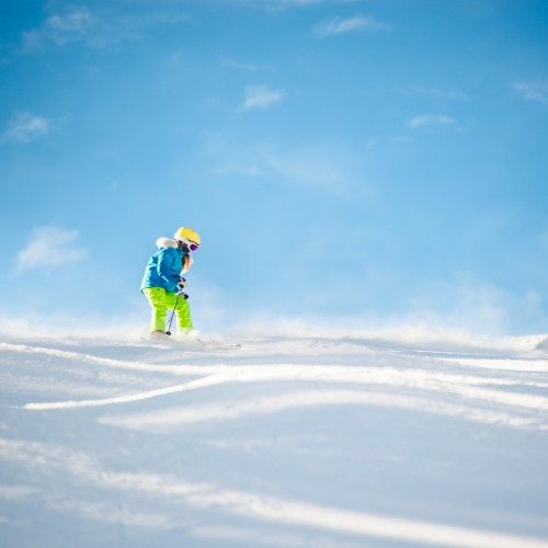 Girl in bright colored ski clothes skiing