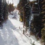 Riding a chair lift through trees in winter