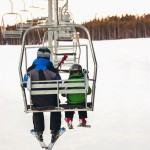 Boy and his father rdiing a chair lift