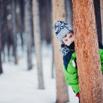 Boy peeking out from behind a pine tree in the snow