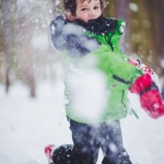 Boy throwing a snowball directly at camera