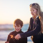 Boy and girl lighting sparklers at the beach at sunset