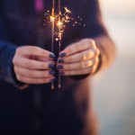 Girl with painted fingernails holding sparklers