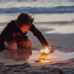 Boy playing with firework sparklers at the beach at sundown