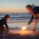Children playing with sparklers at the beach at sunset