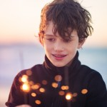 Boy holding sparklers at sunset