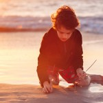 Boy playing with sparklers at the beach at sunset