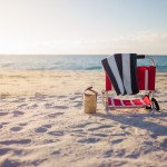 Beach chair on sand at ocean edge