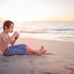 Boy blowing bubbles at the beach at sunset