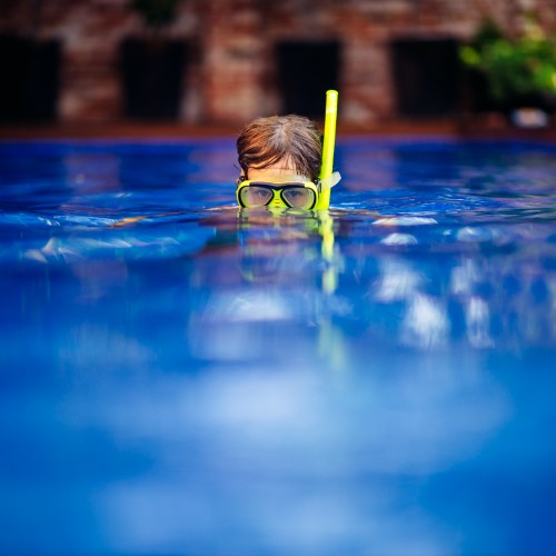 Boy wearing a snorkel set in a pool
