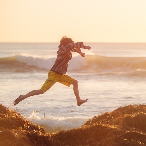 Boy jumping on a large seaweed mound at the beach at sunset
