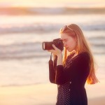 Teenage girl taking photos with a dSLR at the beach at sunset