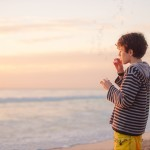 Boy with bubble mix blowing bubbles at the beach at sunset