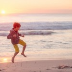 Boy in mid leap while busting some moves at the beach at sunset