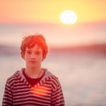 Boy gazes directly at camera while the sun sets behind him