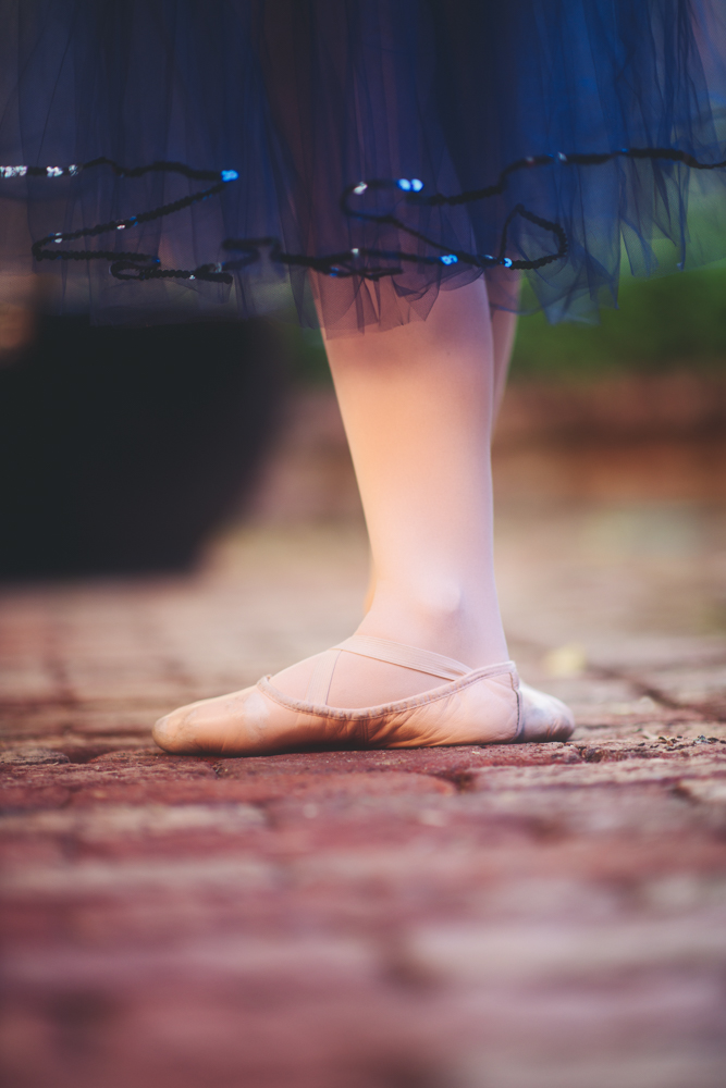 Feet in worn ballet shoes below a navy tulle skirt