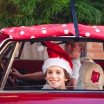 Boy wearing a santa hat smiles while sitting in a red car with a