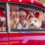 Close up of happy children with a dog in a red car at christmas